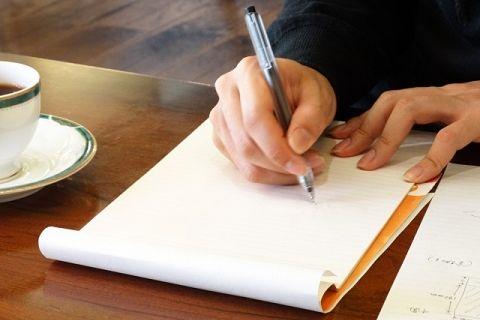 ペンを持って文章を書いている男性